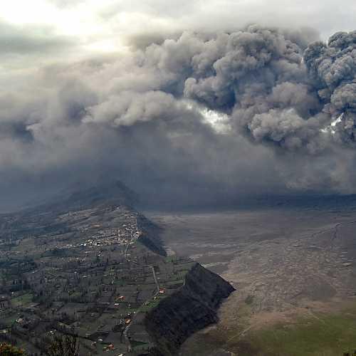 Деревушка Чеморо Лаванг под извергающимся вулканом Бромо.