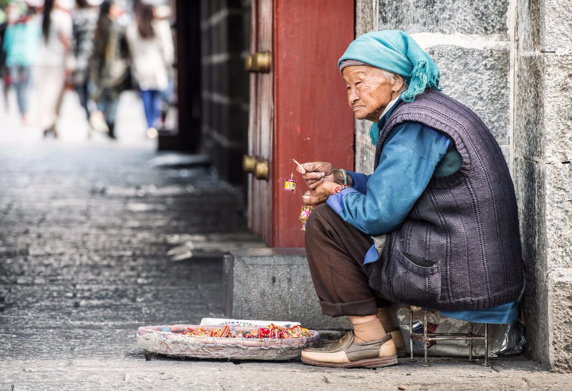 Бабушка с молитвенными барабанчиками на улице Дали.