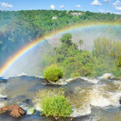 Красочная радуга над водопадом Игуасу на границе Бразилии и Аргентина.