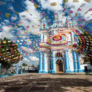 Красочный и волшебный город Сан Кристобаль де Лас Касас. Голубое небо и цветные флаги.