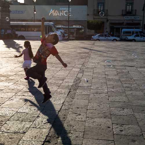 Закатный свет и счастливые дети в городке Морелия.