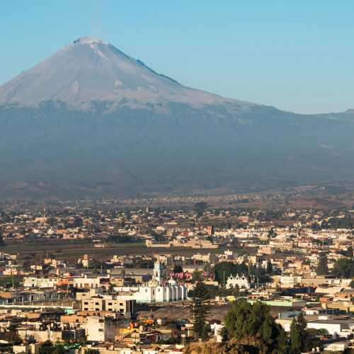 Мексиканский городок Чолула на фоне вулкана Попокатепетль.