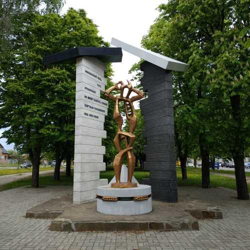 Пам'ятник жертвам Голодомору 1932—1933 років (Суми, Україна).<br/>  <br/> Встановлено на вулиці Степана Бандери в сквері Пам'яті Жертв Голодомору неподалік Сумського автовокзалу, на околиці міста.<br/> <br/> Це образ традиційної української оселі з трисхилою стріхою, від якої зосталося тільки дві стіни (паралельні стели) — біла, що є ознакою колишнього достатку та родючості, і чорна як символ злиднів і відчаю, які приніс комуністичний терор голодом.<br/> <br/> Посередині хати розташована бронзова людська постать — символічний силует жінки, яка схопилася руками за голову. Жорна з колосками, що лежать під ногами жінки — символічне втілення українського достатку та рясного врожаю, що були конфісковані окупантом. Піраміда на задньому плані символізує вічну пам'ять загиблим від рук російських комуністів.