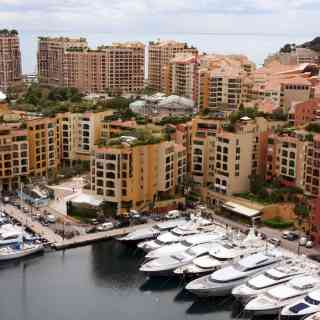 Mooring with yachts near many-storeyed buildings behind which the sea is visible