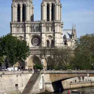 Pleasure boat floating on the river Seine in the background of the Notre Dame de Paris
